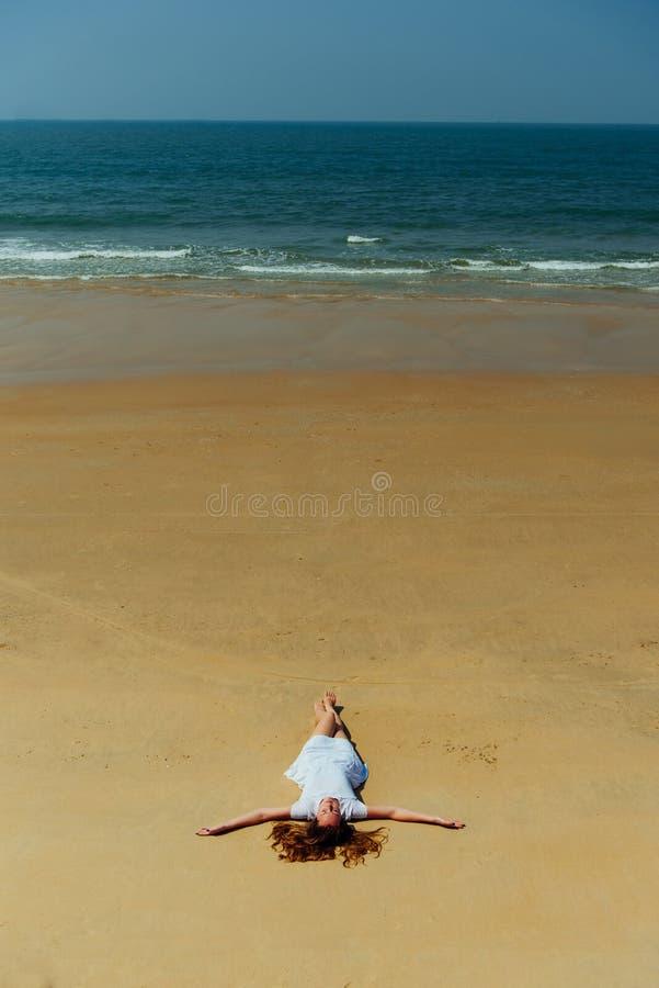 Manierschot van een mooi meisje in een witte kleding die op het strand liggen Goa India royalty-vrije stock afbeeldingen
