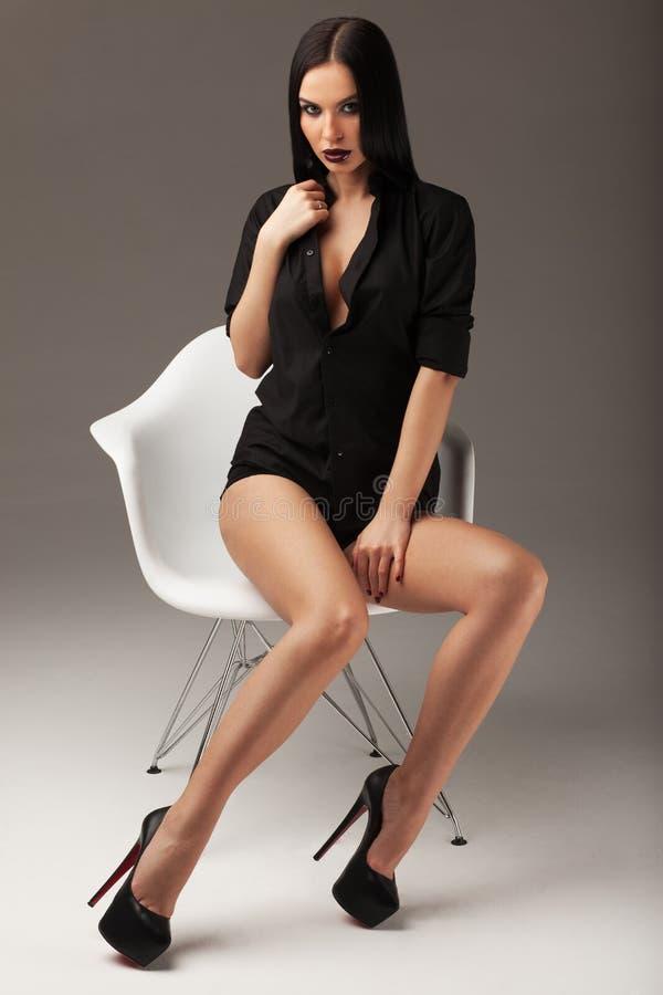 Manierschot van een mooie sexy donkerbruine vrouw die met lang recht haar, zwart overhemd en zwarte schoenen op de stoel zitten stock afbeeldingen