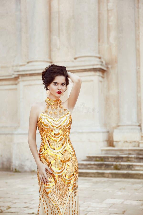 Manierschot van het overweldigen van elegante vrouw in luxueuze gouden kleding royalty-vrije stock foto