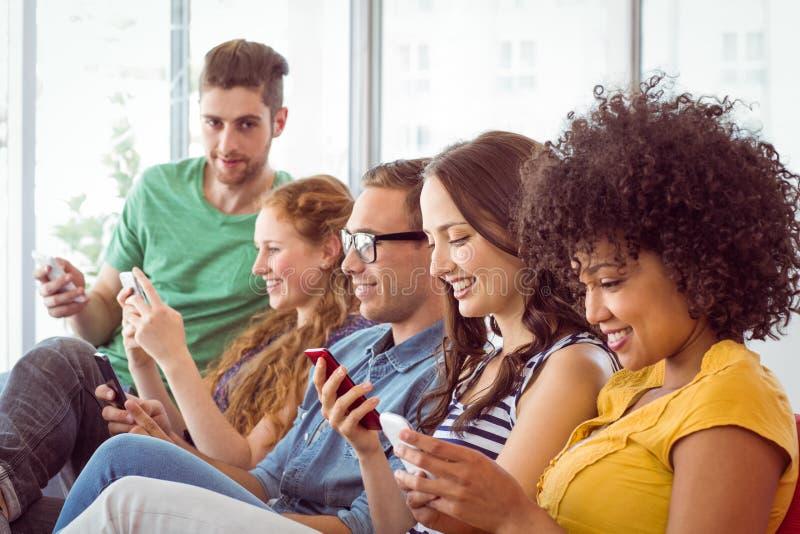 Manierstudenten die hun smatphone bekijken royalty-vrije stock foto