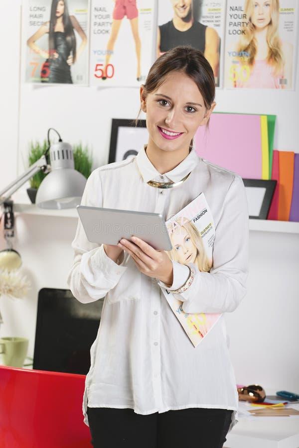 Maniervrouw die blogger in een creatieve werkruimte met cijfer werken royalty-vrije stock afbeelding