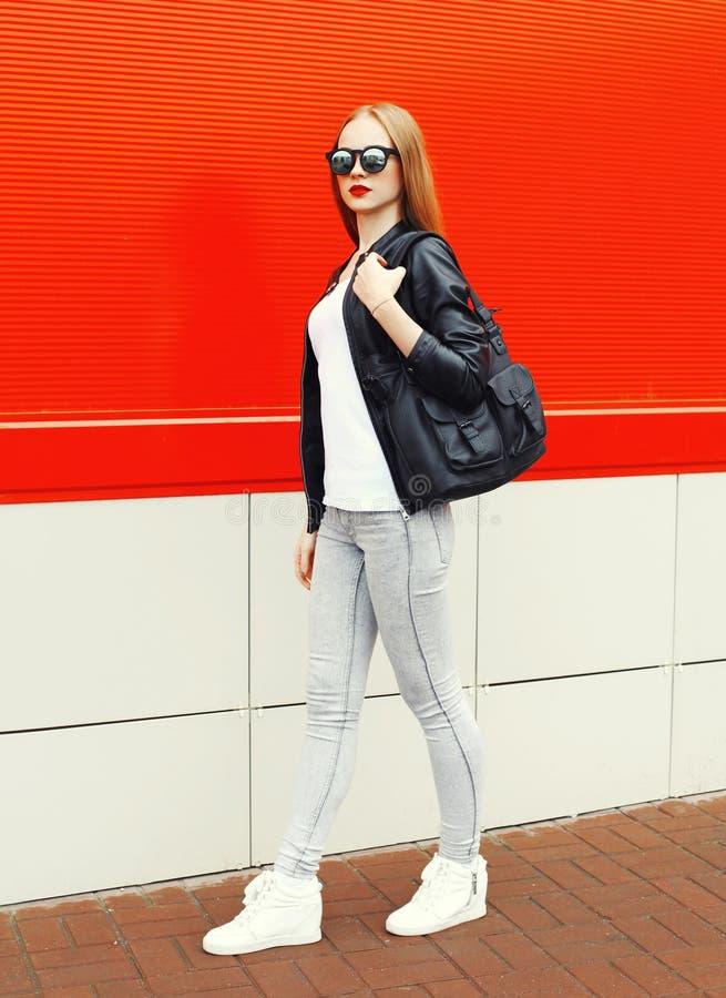 Maniervrouw die een rots zwart jasje, zonnebril en zak dragen die in stad over rood lopen stock afbeeldingen