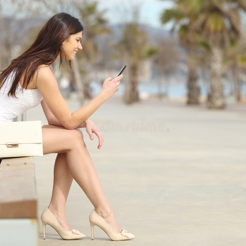Maniervrouw die een smartphone in de straat gebruiken stock fotografie