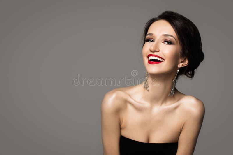 Maniervrouw die op een grijze achtergrond lachen royalty-vrije stock afbeelding