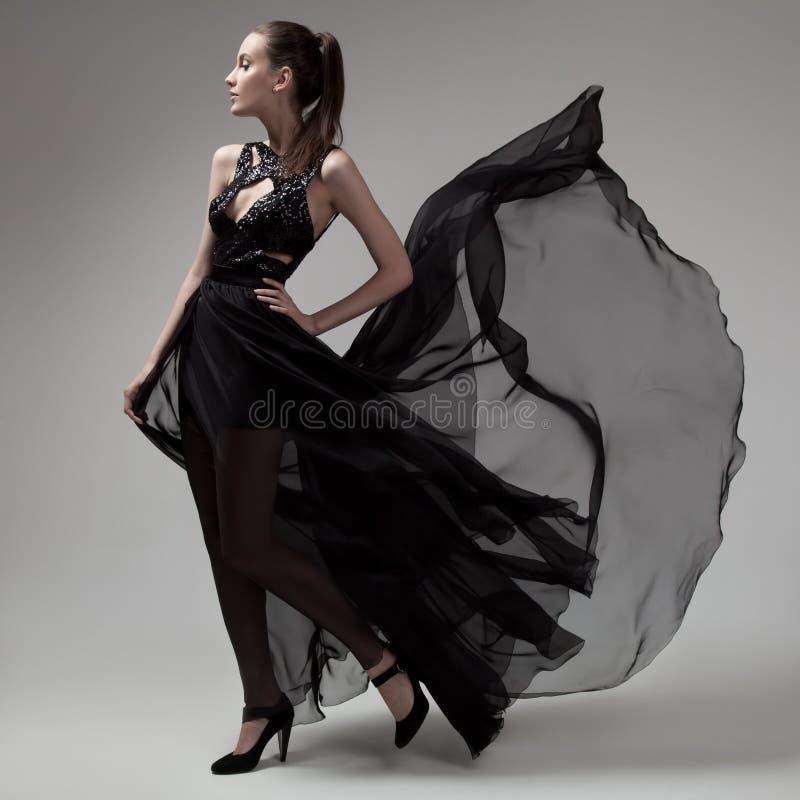 Maniervrouw in fladderende zwarte kleding Grijze achtergrond stock foto