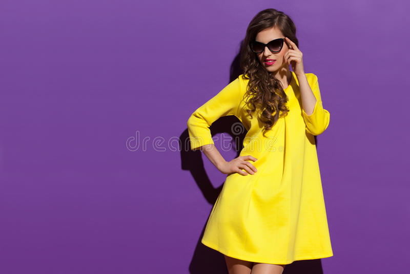 Maniervrouw in Geel Mini Dress And Sunglasses Looking weg royalty-vrije stock foto's