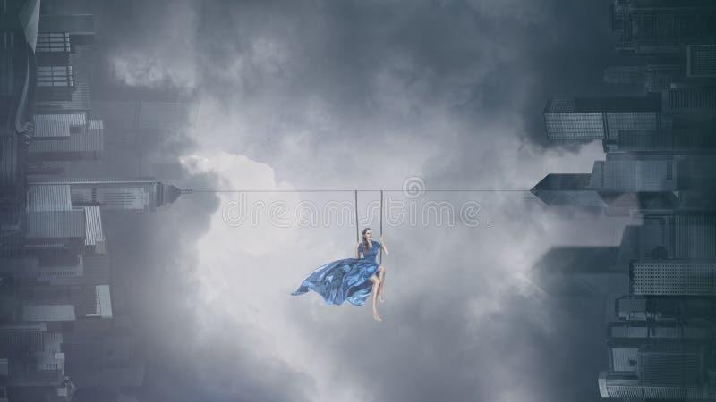 Maniervrouw op schommeling boven stad stock fotografie