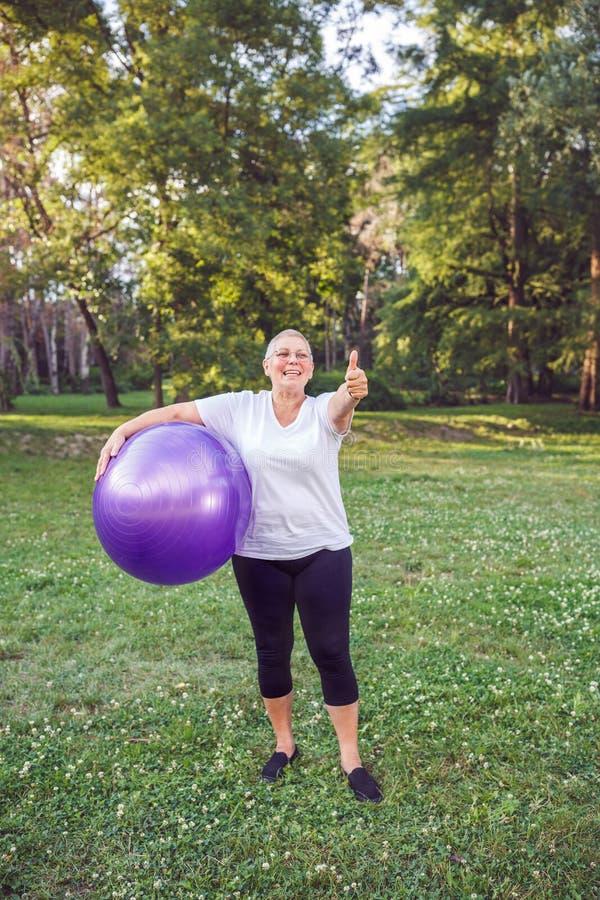 Maniez maladroitement pour l'exercice sain - femme heureuse de retraité avec l'ajustement images stock