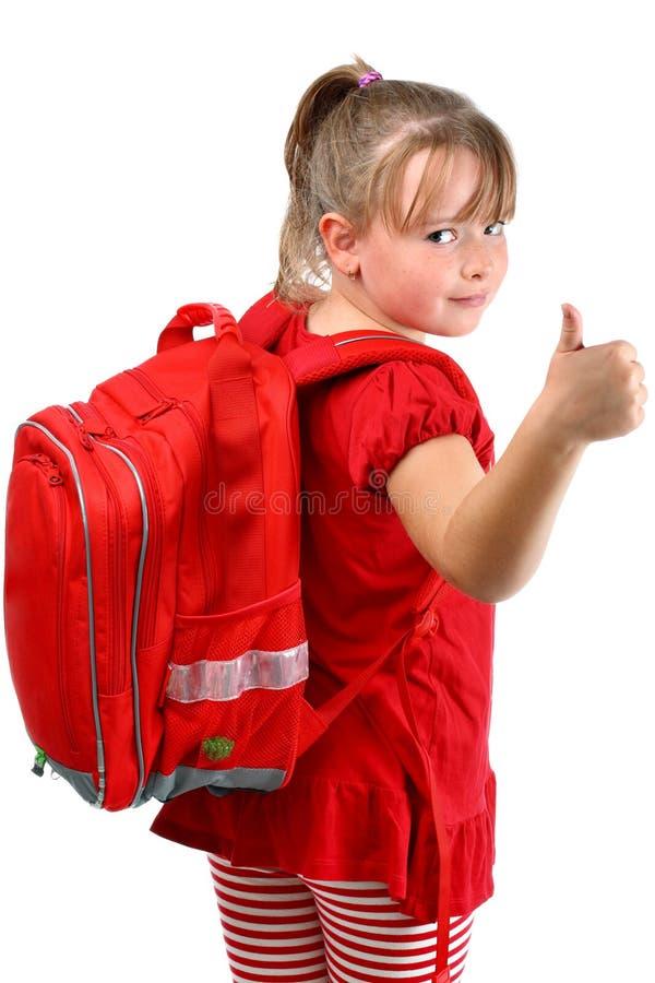 Maniez maladroitement vers le haut de la fille avec le cartable rouge d'isolement sur le blanc images libres de droits