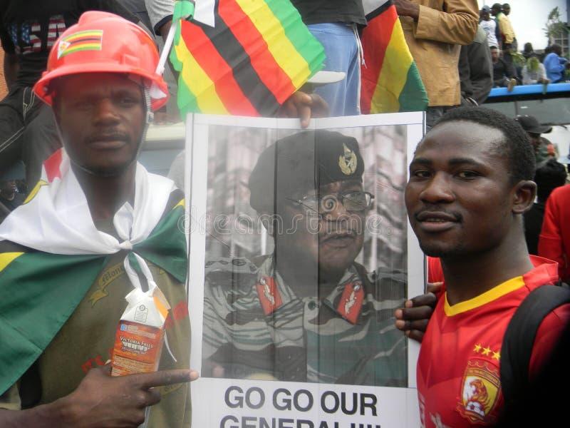 Manifestante anti de Mugabe con el potrait de general Chiwenga fotos de archivo