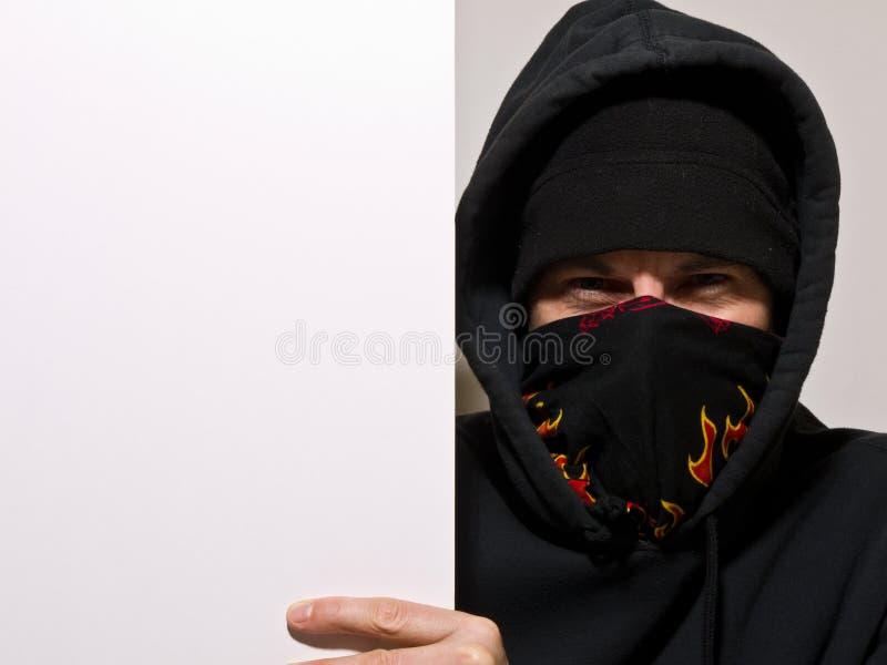 Manifestante encapuchado que lleva a cabo una muestra en blanco fotos de archivo libres de regalías