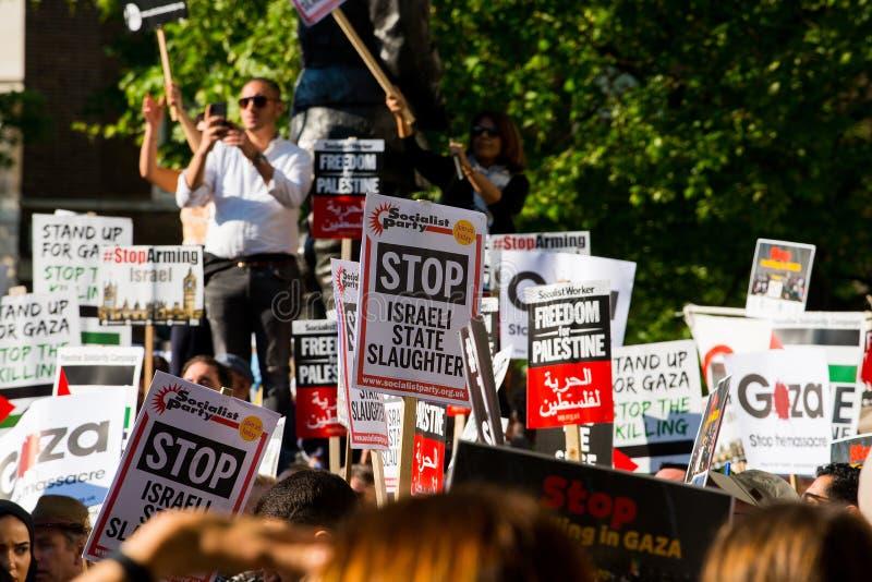 Manifestantes con los carteles en Gaza: Pare la reunión de la masacre en Whitehall, Londres, Reino Unido imagenes de archivo