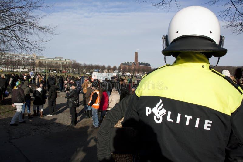 Manifestantes de observación del oficial de policía foto de archivo libre de regalías