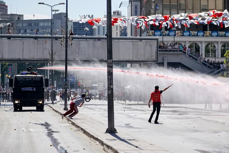 Manifestantes que luchan contra el canon del agua de la policía mientras que tira la corriente de la alta velocidad del agua dura fotos de archivo