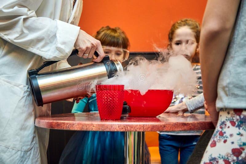 Manifestazione chimica per i bambini Professore ha effettuato gli esperimenti chimici con azoto liquido sulla bambina di complean fotografie stock