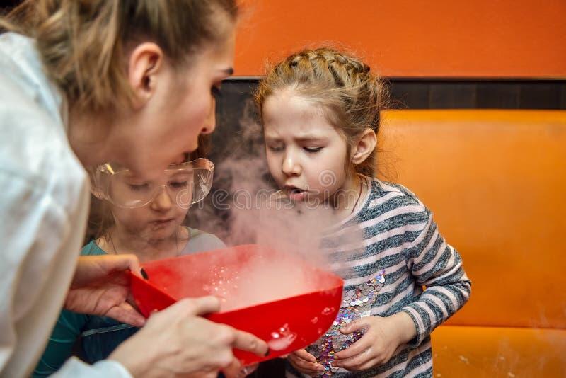Manifestazione chimica per i bambini Professore ha effettuato gli esperimenti chimici con azoto liquido sulla bambina di complean immagine stock libera da diritti