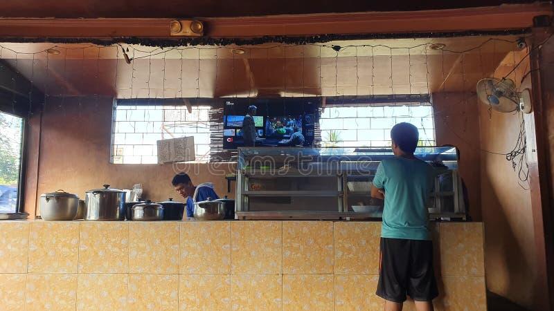 Manifestazione a Davao del Sur, Filippine: un uomo guarda un film gratis a Eatery fotografia stock libera da diritti