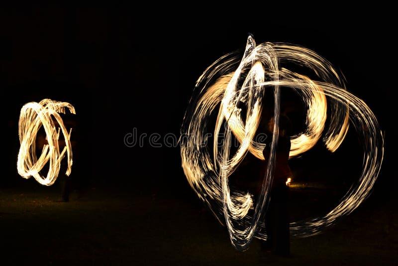 Manifestazione del fuoco - artisti che manipolano con gli strumenti brucianti nello scuro fotografia stock libera da diritti