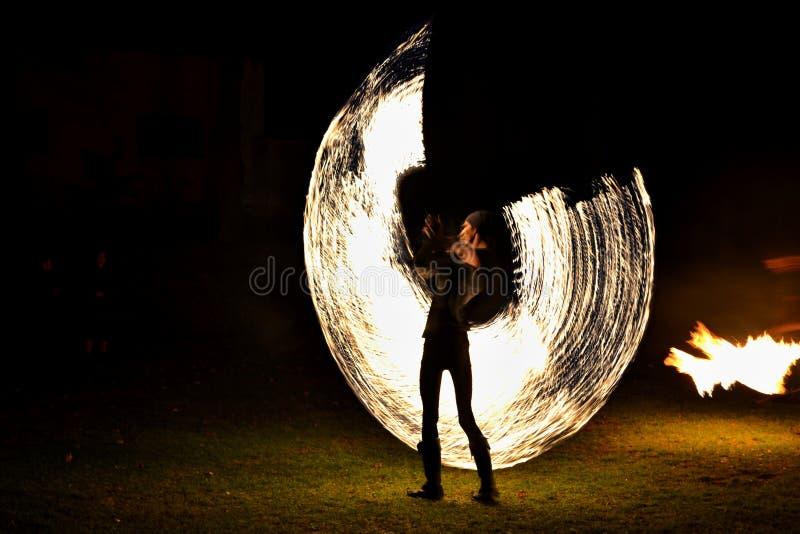 Manifestazione del fuoco - artisti che saltano sopra un salto della corda bruciante nello scuro immagine stock libera da diritti