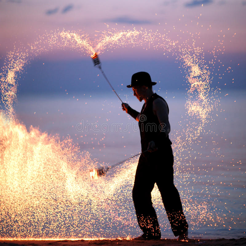 Manifestazione del fuoco sulla spiaggia al tramonto fotografia stock libera da diritti