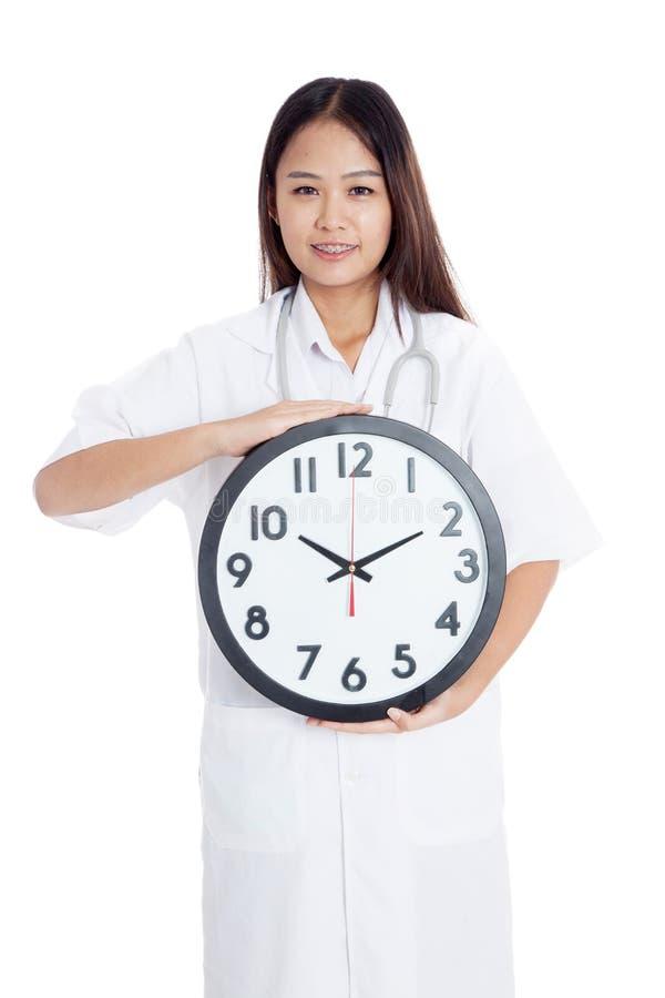 Manifestazione felice di giovane medico femminile asiatico un orologio fotografia stock libera da diritti