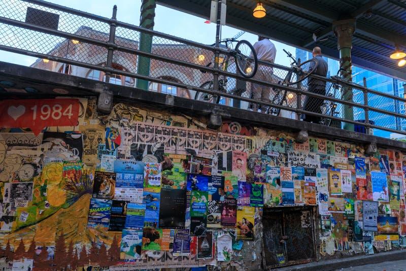 Manifesti lacerati variopinti sulle vecchie pareti di lerciume al mercato di posto di luccio a Seattle fotografia stock
