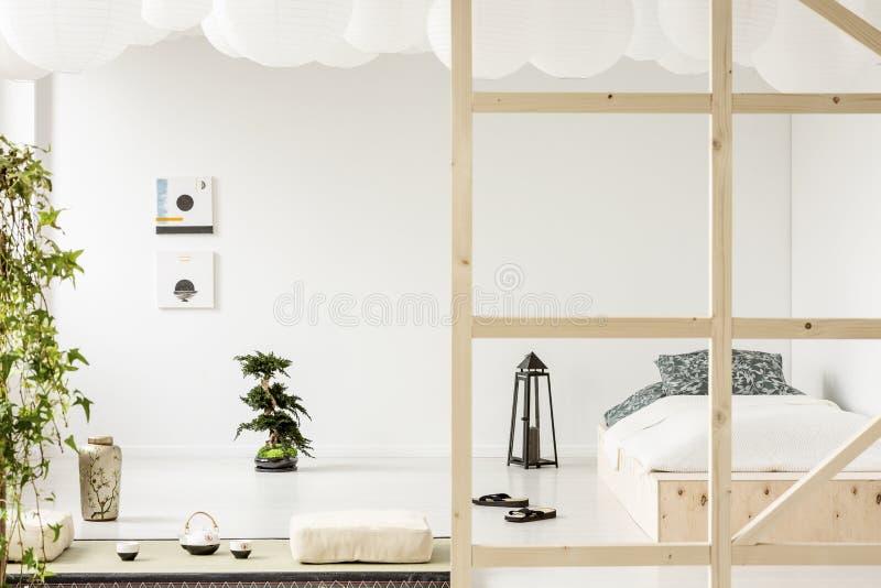 Manifesti sulla parete bianca sopra i bonsai nell'interno della camera da letto con la lanterna fotografie stock