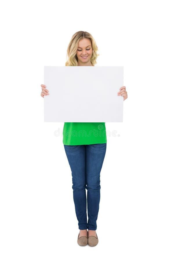 Manifesto biondo sveglio sorridente di bianco della tenuta immagine stock libera da diritti