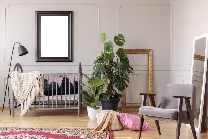 Manifesto del modello nell'interno grigio della stanza del bambino con le piante verdi e la retro poltrona, fotografia stock