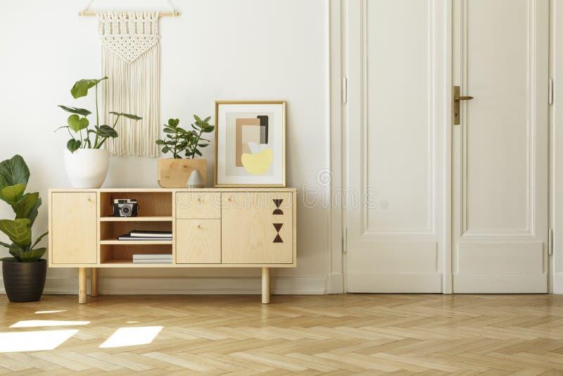 Manifesto e pianta sull'armadietto di legno nell'interno del salone con immagini stock