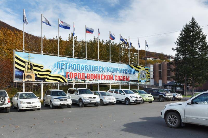 Manifesto Petropavlovsk-Kamcatskij - città di gloria militare e aste della bandiera con le bandiere del funzionario di volo immagine stock