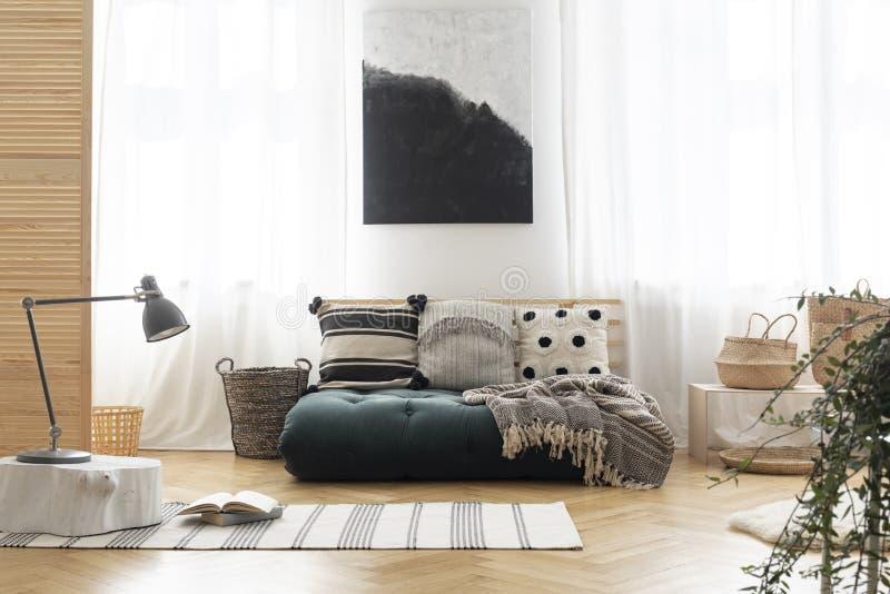 Manifesto sopra il futon verde con i cuscini modellati immagine stock libera da diritti