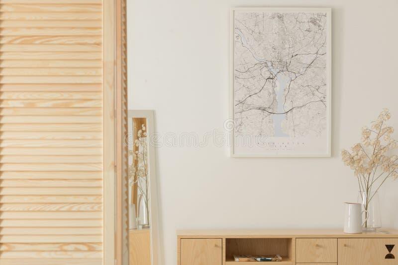 Manifesto sulla parete bianca sopra il gabinetto di legno con la decorazione nell'interno minimo dell'anticamera Foto reale immagini stock libere da diritti