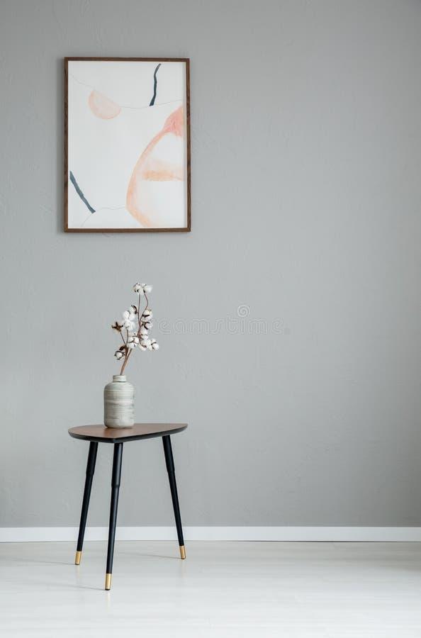 Manifesto sulla parete grigia nell'interno minimo del salone con i fiori bianchi sulla tavola di legno fotografie stock