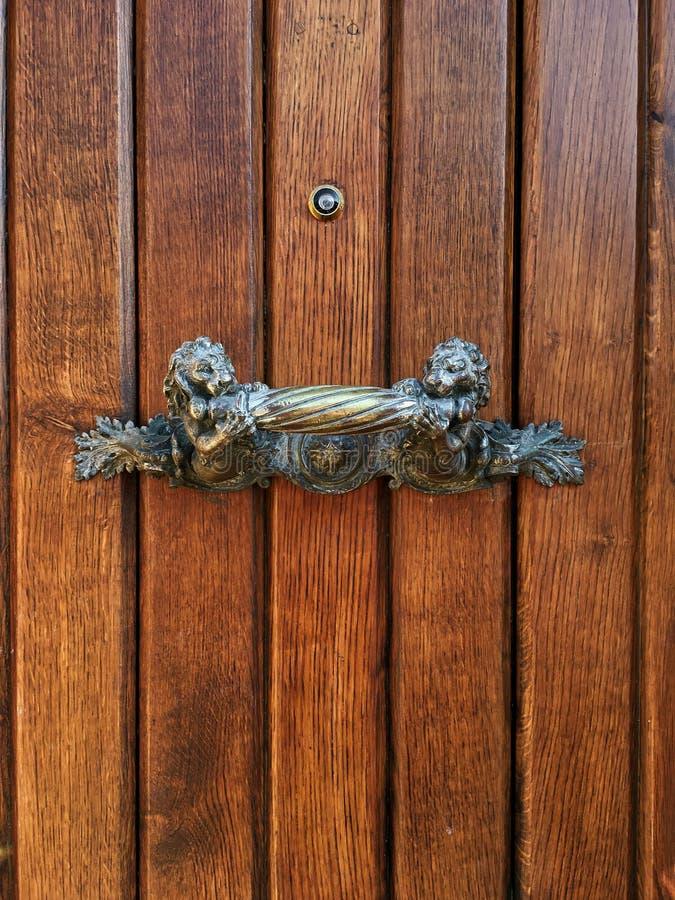 Maniglia bronzea antica di tirata c Maniglia di porta medievale antica di tirata Maniglia forgiata sulla porta di legno Maniglia  fotografie stock libere da diritti