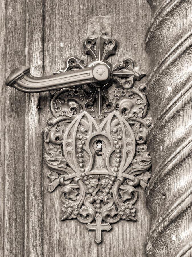 Maniglia della porta d'annata sulla porta antica con l'incrocio fotografie stock