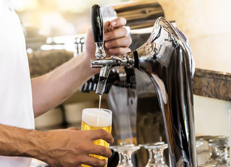 Maniglia di Barman al rubinetto della birra versando un bicchiere di birra fotografia stock libera da diritti