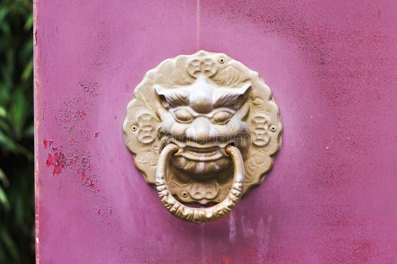 Maniglia di porta dorata - battitore in una porta di legno viola fotografia stock