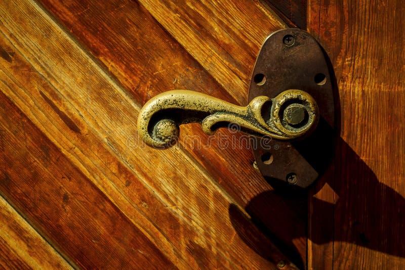 Manija de bronce vieja en la puerta de madera fotos de archivo libres de regalías