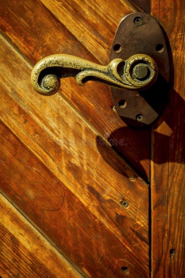 Manija de bronce vieja en la puerta de madera imagen de archivo libre de regalías