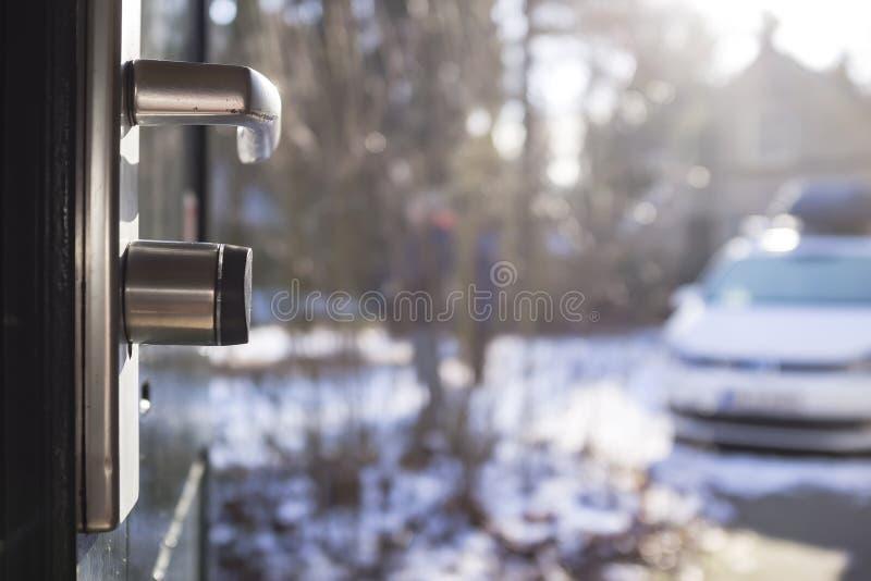 Manija de Chrome con una cerradura en la puerta principal abierta del metal, contra el fondo borroso del patio, en los rayos bril fotos de archivo