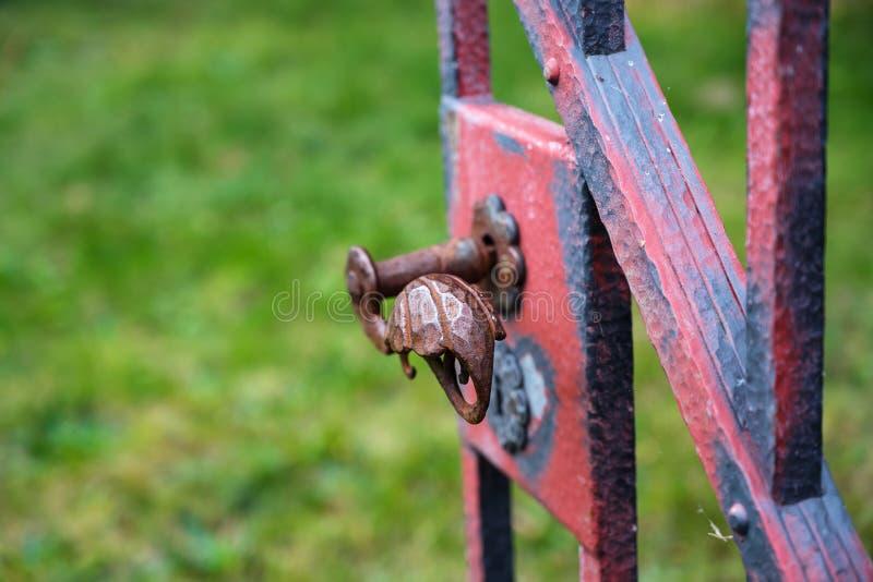 Manija del hierro labrado en una vieja puerta de jardín abierta con la cuesta roja gastada imagen de archivo