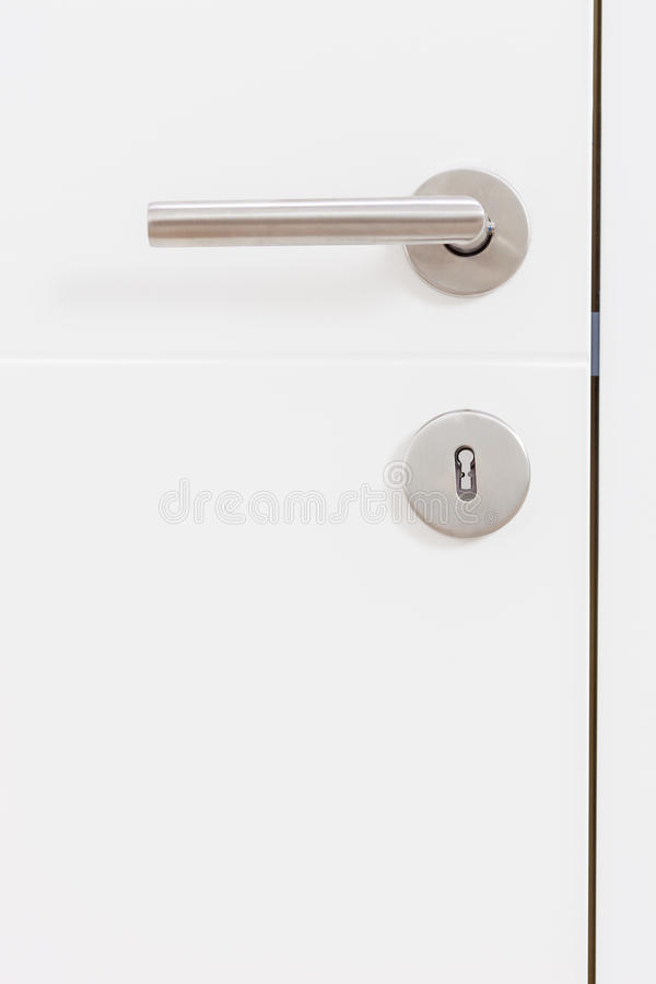 Manija gris del metal en una puerta blanca fotografía de archivo
