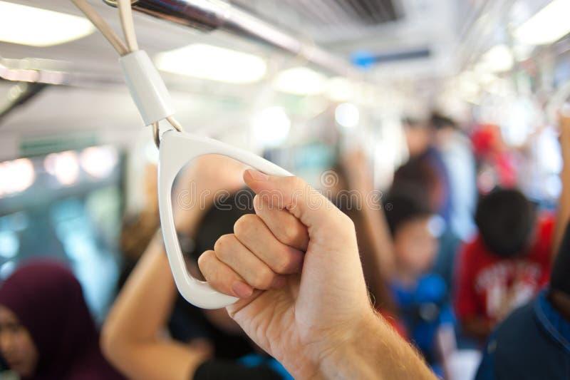 Manija masculina de la tenencia de la mano en el metro público foto de archivo libre de regalías