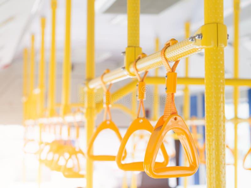 Manijas plásticas amarillas del primer para la seguridad de los pasajeros de situación en el autobús foto de archivo libre de regalías