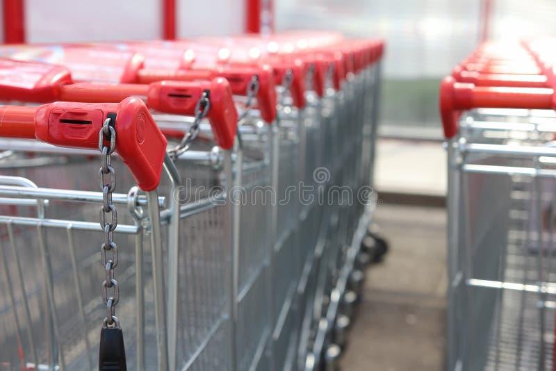 Manijas rojas de las carretillas de las compras que se colocan en fila cerca de hipermercado Primer de la carretilla de las compr imagen de archivo