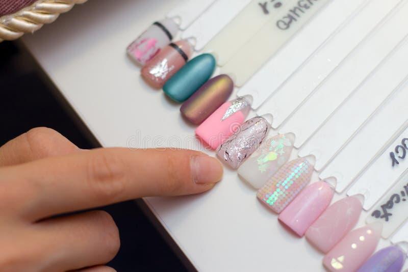Maniküre- und Nagelpflegekonzept Eine Frau in einem Schönheitssalon hält farbige TestNagellacke mit verschiedenen Farben und wähl stockbild