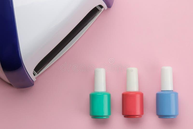 maniküre UVlampe und Nagellack auf einem leichten rosa Hintergrund Manikürezusätze und -werkzeuge für Nägel Beschneidungspfad ein stockbilder