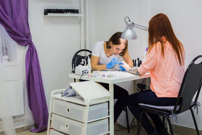 Manikürist, der Kunden am Schönheitssalon - Malerei auf dem Nagel behandelt stockfotografie