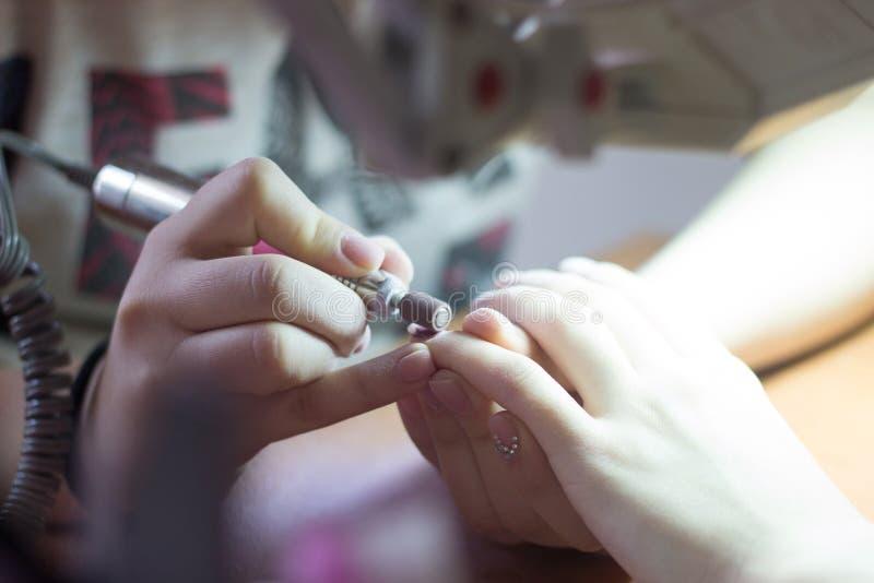 Manikürist macht Maniküreverfahren mit einer Maschine auf Maniküre t lizenzfreie stockbilder